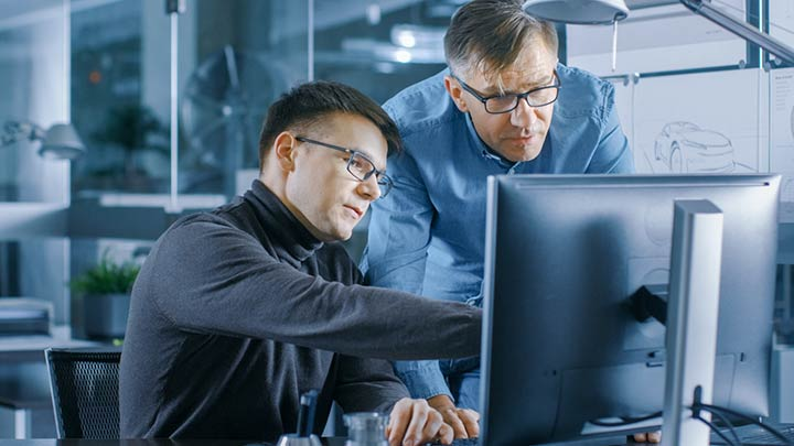 two men looking at a computer screens